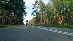Ein Motorradfahrer reitet ein rotes Fahrrad auf eine Straße stock footage