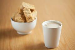 Ein mugg des Kaffees mit einer Schüssel Zwiebacken im Hintergrund Stockbild