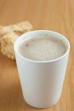 Ein mugg des Kaffees mit Zwiebacke im Hintergrund Stockfoto