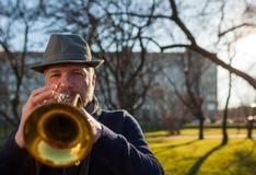 Ein Musiker der älteren Personen spielt in der Straße auf einer Trompete stockfoto