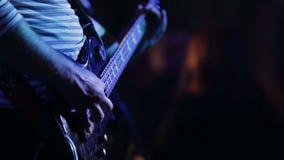 Ein Musiker, der auf Bass-Gitarre spielt stock footage