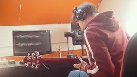 Ein Musikermann in den Kopfhörern, die Gitarre spielen und den Ton im Studio notieren Betrachten des Monitors stock video footage