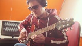 Ein Musikermann in den Kopfhörern, die Gitarre spielen und den Ton im Studio notieren stock video