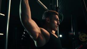Ein muskulöser Mann, der Übungen auf den Muskeln seiner Schultern tut, setzt die Messlatte in einer dunklen Turnhalle höher an un stock video