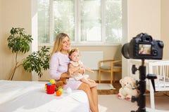 Ein Mutter Blogger mit einem Kind notiert Video auf der Kamera Stockfotografie