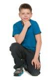 Nachdenklicher Junge im blauen Hemd sitzt auf dem Boden Stockfotos