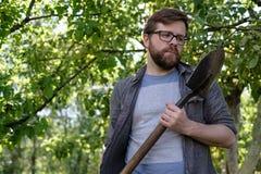 Ein nachdenklicher Manngärtner überprüft eine Schaufel, die in seinen Händen, gegen den Hintergrund von Apfelbäumen, an einem Som lizenzfreie stockfotografie