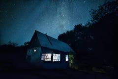 Ein Nachtfoto eines ländlichen einfachen Bauernhauses und des sternenklaren Himmels über ihm Stockbilder