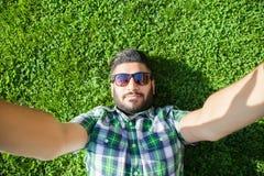Ein nahöstlicher Mann der jungen Mode mit Bart und Modefrisur liegt auf einem Gras in einem Park, der selfie nimmt Stockbilder