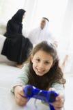 Ein nahöstliches Mädchen, das ein Videospiel spielt Stockfoto