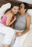 Ein nahöstliches Paar, das auf einem Bett liegt Stockfotografie