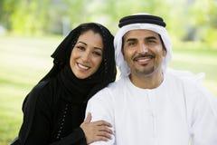 Ein nahöstliches Paar, das in einem Park sitzt Stockfotos