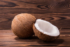 Ein Nahaufnahmepaar tropische Kokosnüsse auf einem dunkelbraunen hölzernen Hintergrund Ein exotischer ganzer brauner Coco und ein stockfotografie