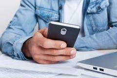 Ein Nahaufnahmeporträt männlicher ` s Hand, die Smartphone in seiner Hand hält, kleidete im Baumwollstoffhemd an, das im Büro sit Lizenzfreie Stockfotos