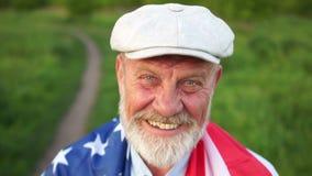 Ein nahes Porträt eines Rentners von Texas auf uns Unabhängigkeitstag am 4. Juli Wir Flagge auf Schultern stock footage