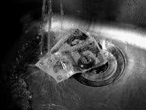 Ein nasser BRITISCHER Pfund-Münzen-Stapel durch ein Ablaufloch stockfotos