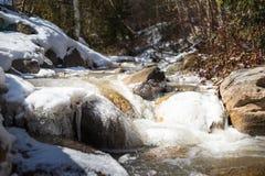 Ein Nebenfluss l?sst letztes Eis laufen und Schnee bedeckte Flusssteine stockbilder