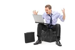 Ein nervöser junger Geschäftsmann, der auf seinem Laptop schreit Lizenzfreie Stockbilder