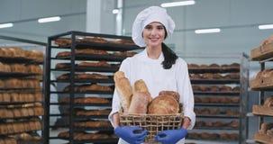 Ein netter Bäcker der jungen Frau des Landes in einer Backwarenindustrie, die einen Korb mit frischem Brot und das Lächeln nett h stock video