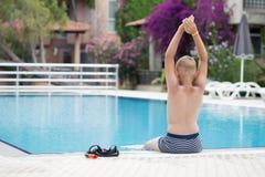 Ein netter blonder Junge, der lernt zu schwimmen Stockfoto