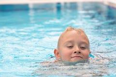 Ein netter blonder Junge, der lernt zu schwimmen Lizenzfreies Stockbild