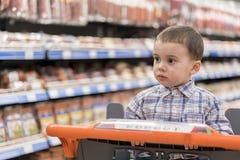 Ein netter Junge kleidete in einem karierten Hemd in einem Supermarkt in einer Laufkatze an Vor dem hintergrund der Regale mit Fl Stockbilder