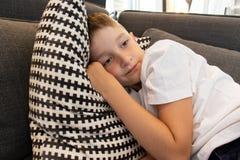 Ein netter Junge liegend auf einem Sofa und einem Kopf auf kariertes Schwarzweiss-Kissen gesetzt lizenzfreie stockfotos