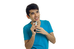 Ein netter junger Mann in ein T-Shirt Rasuren und Blicken in Richtung zu Stockfoto