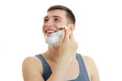 Ein netter junger Mann mit Schaum auf seinem Gesicht blickt in Richtung der Maschine und rasiert seinen Bart Stockfoto