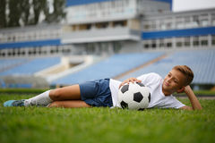 Ein netter Kerl mit einem Fußball, der auf ein grünes Gras und auf einen Stadionshintergrund legt Ein Fußballspieler im Freien Lizenzfreies Stockbild