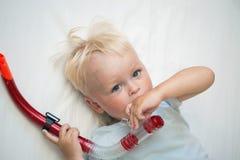 Ein netter kleiner Junge, der mit dem Schnorcheln des Rohrs spielt Lizenzfreie Stockfotos