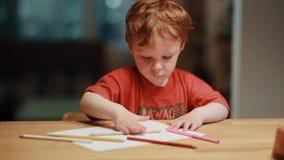 Ein netter kleiner Junge, der am Tisch sitzt und mit den farbigen Bleistiften auf Weißbuch zeichnet stock footage