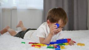 Ein netter kleiner Junge liegt auf dem Bett und spielt mit farbigen Blöcken Kindergestalten vom meccano stock footage