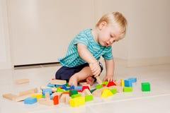 Ein netter kleiner Junge spielt mit bunten Blöcken Stockfotos