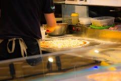 Ein netter Pizzahersteller beim Arbeiten mit dem Ofen, der eine seiner ausgezeichneten Pizzas einfügt lizenzfreie stockfotografie