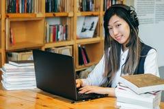 Ein nettes asiatisches Mädchen sitzt in der Bibliothek in einem großen Kopfhörer, umgeben durch die Bücher und arbeitet auf einem stockfotos