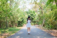 Ein nettes asiatisches thailändisches Mädchen steht auf einem Waldweg allein Stockbild