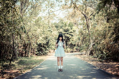 Ein nettes asiatisches thailändisches Mädchen steht auf einem Waldweg allein im vin Stockbild