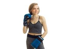 Ein nettes athletisches Mädchen mit einem Zopf und Boxhandschuhen blickt in Richtung Lizenzfreies Stockbild