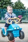 Ein nettes Baby, das ein großes Spielzeugauto auf einem Sommerspielplatz fährt Stockbilder