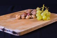 Ein nettes Bild von Mischnüssen und von Trauben auf einer Holzoberfläche Stockbild