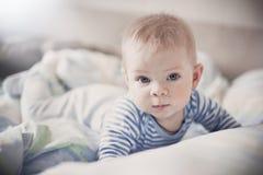 Ein nettes blondes Baby liegt in einem hellen Bett und betrachtet mit blauen Augen der Kamera Lizenzfreies Stockfoto