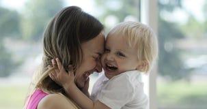 Ein nettes blondes Kind umarmt eine junge Mutter in der Front durch das große Fenster stock video