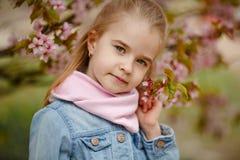 Ein nettes blondes Mädchen lächelt gegen einen Hintergrund von rosafarbenen Kirschblüte-BU lizenzfreie stockbilder