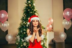 Ein nettes junges Mädchen in einem roten hellen Santa Claus New Year-Kostüm, steht in einem geräumigen hellen Raum mit einem ausg stockfotos