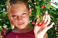 Ein nettes junges Mädchen und eine rote Kirsche Lizenzfreies Stockfoto