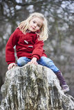 Ein nettes Kinderblondes Mädchen, das draußen auf einem Felsen aufwirft Lizenzfreies Stockfoto