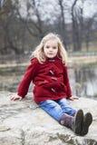 Ein nettes Kinderblondes Mädchen, das draußen auf einem Felsen aufwirft Lizenzfreie Stockfotos