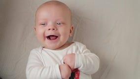 Ein nettes kleines Baby untersucht die Kamera und ist auf weißen Bettlaken glücklich stock footage
