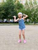 Ein nettes kleines lachendes und machendes Mädchen stellt nettes kleines Mädchen gegenüber Lizenzfreie Stockbilder
